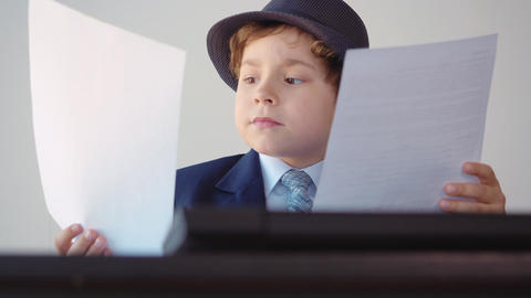Young business boy reading business documents sitting at table in work office Live Action