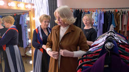 Mature woman trying new jacket front mirror while shopping in fashion shop Footage