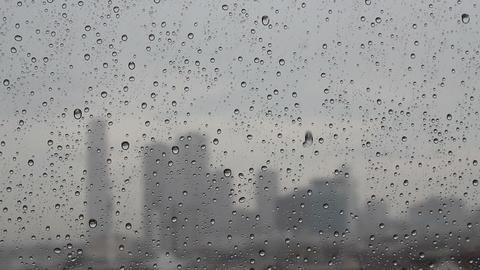 Rain drops flowing through glass window, silhouette of city,rain drops on window Live Action