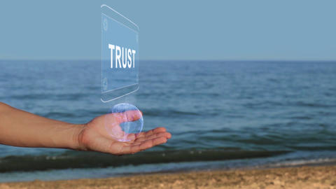 Hands on beach hold hologram text Trust Footage