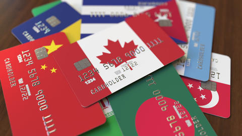 Many credit cards with different flags, emphasized bank card with flag of Canada Footage