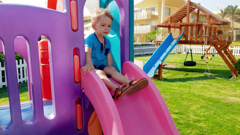 4k footage of cheerful smiling toddler boy riding on the slide at children Footage