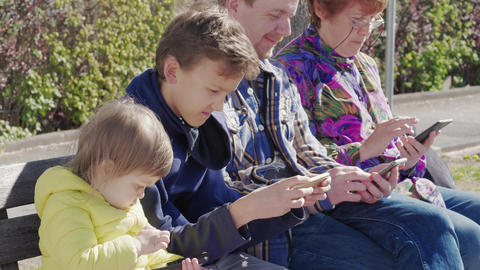 Modern communication: family with mobile phones outdoor, day Footage