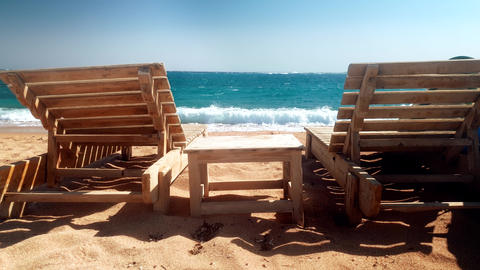 4k video of two wooden sunbeds and small table on the abandoned sea beach Live Action