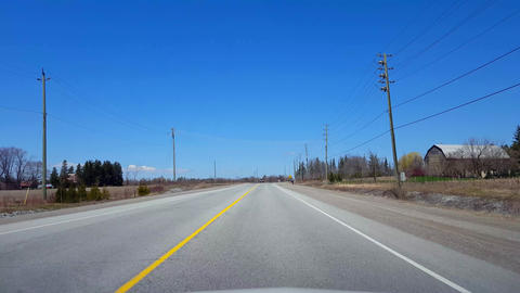 Driving Rural Road Along Farmland During Spring Day. Driver Point of View POV Beautiful Sunny Footage