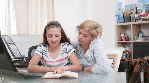 Loving mother and her teenage girl reading a book together Footage