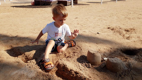 4k footage of little toddler boy sitting on the sea beach and building castle Footage