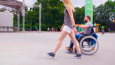 Young disable man walking in the park with his wife Live Action