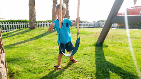 4k footage of cheerful toddler boy playing on the playground with swing at sunny Footage
