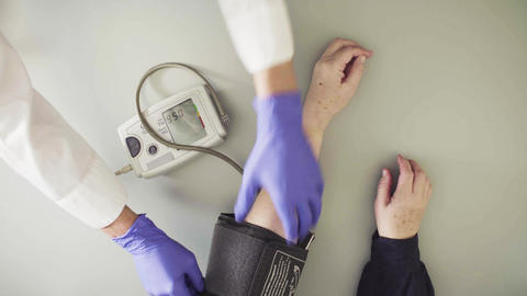 Doctor measuring blood pressure to senior woman Live Action