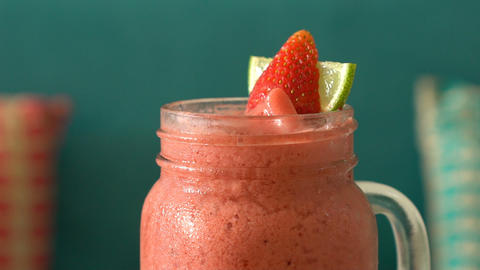 Fresh tropical organic strawberry smoothie rotate on table Live Action