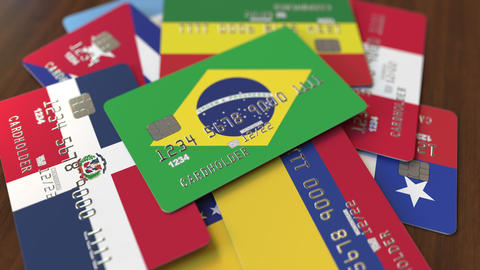 Many credit cards with different flags, emphasized bank card with flag of Brazil Live Action