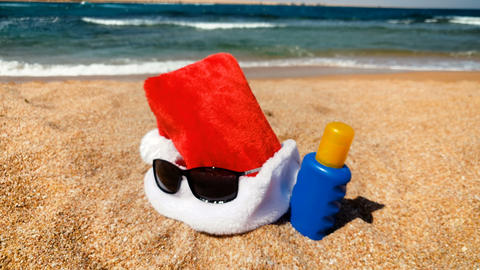 4k footage of Santa hat lying on the sandy beach. Concept of celebrating Footage