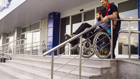 Man helping to move down to a disabled man Live Action