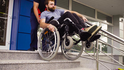 Man helping to move down to a disabled man Footage
