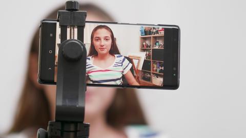Teenage girl filming herself on a smartphone Footage