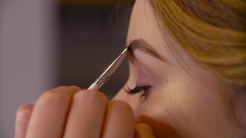 The makeup artist correcting the shape of eyebrow Live Action