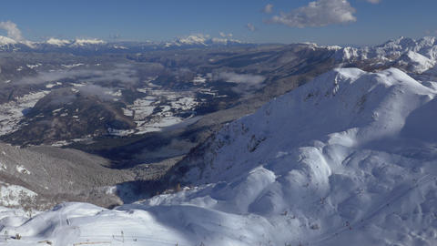 Aerial - Above snow capped mountains with a view into the valley Footage