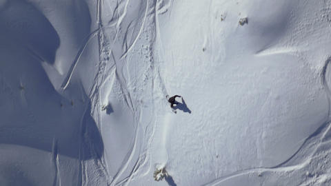 Slow motion - Aerial shot of snowboarder riding in powder snow Footage