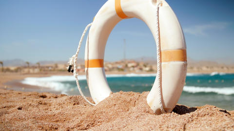 4k beautiful slow motion video of life saving ring buoy digged in the sand on Footage