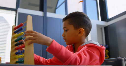 Side view of Asian schoolboy solving math problem with abacus at desk in a classroom at school 4k Live Action