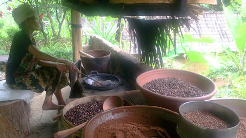 Bali, Indonesia, 10 April 2019: Old woman roasting luwak coffee beans in Ubud Archivo