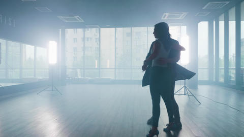 Silhouette of dance partners dancing kizomba in a large studio Live Action
