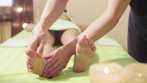 Massage therapist doing massage of a womans foot Footage