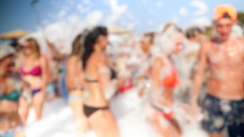 4k video of cheerful crowd in swimsuits and bikinis dancing on the beach at Footage