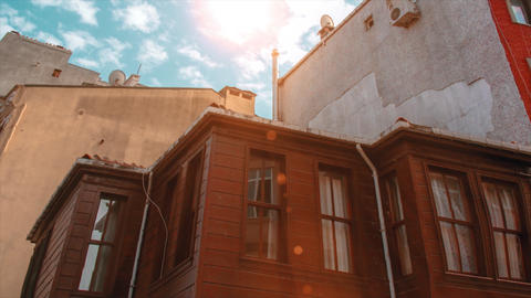 4K Istanbul city's wooden house with sun and clouds. Brown old style house between of apartment Live Action