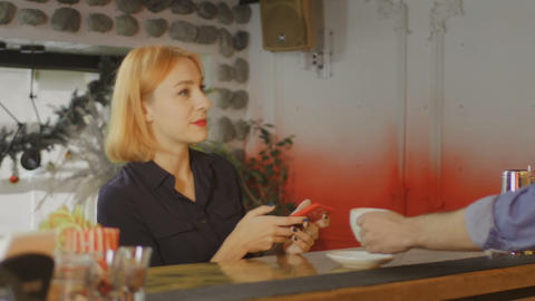 Young beautiful woman typing on cellphone and drinking coffee, bar background Footage