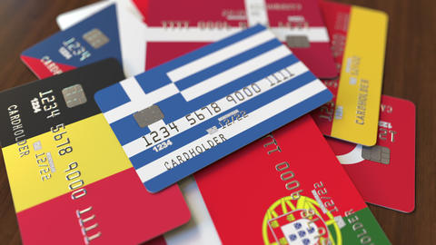 Many credit cards with different flags, emphasized bank card with flag of Greece Live Action