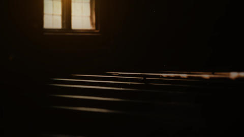 Pews and window in dark. Inside old, historic church; dark atmosphere and reflection of sun Live Action