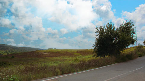 Empty road view with clouds and grass. Beautiful town road with asphalt between foliage Footage