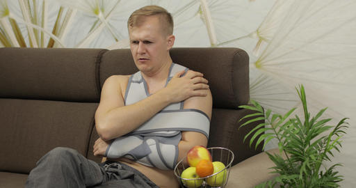 Painful man with a broken arm wearing arm brace sitting on a sofa eating apple Live Action