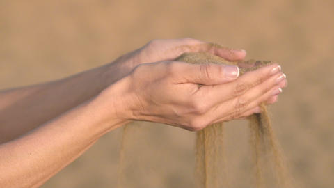Slow motion close up, unrecognizable woman hands grabs a handful of dry sand and Footage