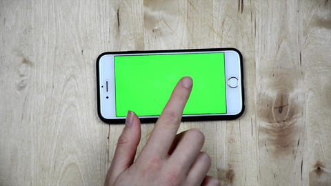 Woman is using smartphone with green screen. Girl's hand using, holding phone. top view. Blank, Live Action
