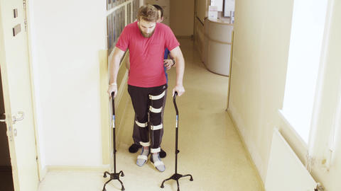 Invalid in orthosis walking with support of two walking cane Live Action