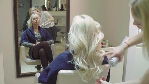 Hairstylist applying hair spray woman's hair Footage