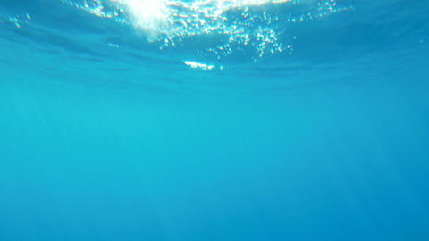 4k slow motion underwater video of sun rays shining through sea surface Live Action