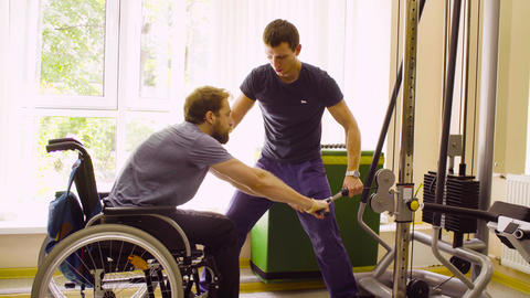 Young disabled man in wheelchair doing strength exercises for hands in the Live Action