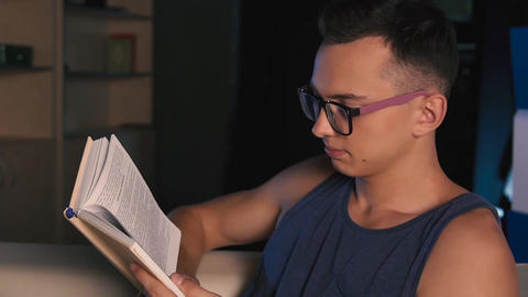 A young man with glasses sitting on a bed reading an interesting book, on a dark Footage