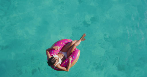 Donut float - Summer Vacation Woman on inflatable donut in swimming pool Footage