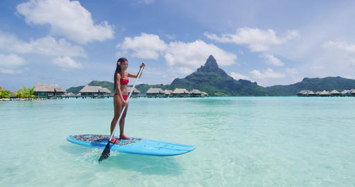 Paddleboard woman relaxing at Bora Bora luxury hotel resort vacation in Tahiti Footage