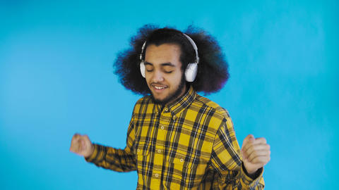 Positive African American man listening music in his headphones on Blue Footage