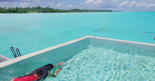 Luxury summer vacation - Woman swimming in infinity pool at hotel resort Footage