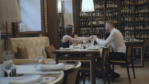 Glamour brunette woman and a handsome bearded blond man sitting at the table in Live Action
