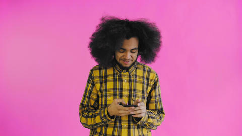 Portrait of African American man with curly hair chatting on smartphone on Footage