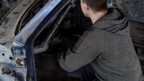 Man examines a broken car Live Action