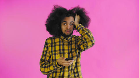 Young sad Afro-American man using phone and getting bad news on purple Live Action
